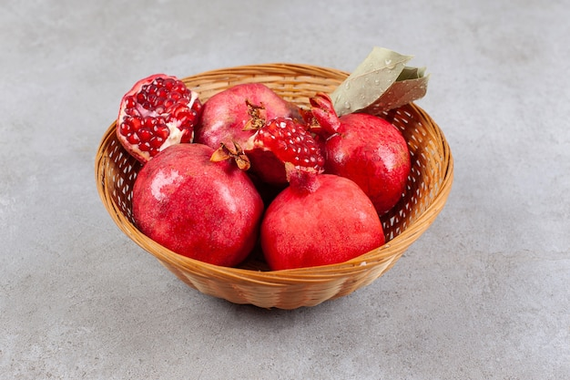 Gehele granaatappels en zaden in houten mand