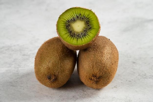 Gehele kiwivruchten en halve kiwivruchten op wit.