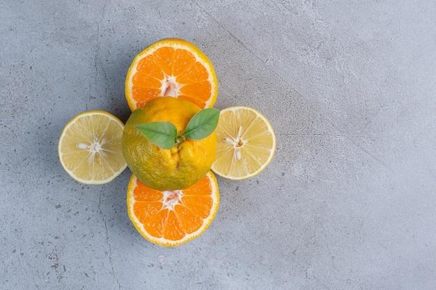 Gehele mandarijn op citroen en mandarijnplakken op marmeren achtergrond.