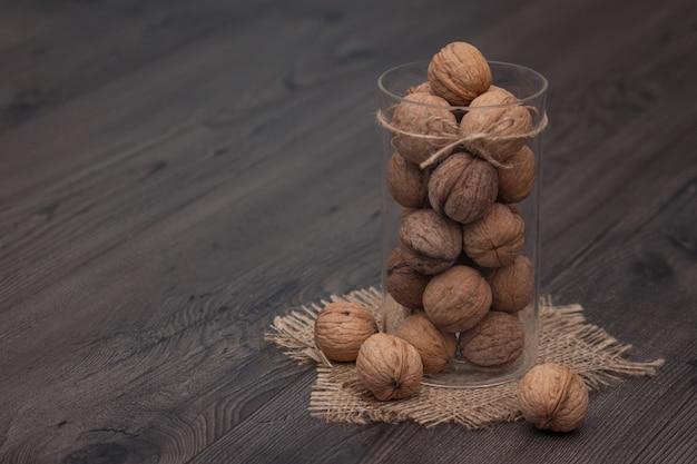 Gehele okkernoten in een glaskruik op een rustieke houten achtergrond. gezond eten, snack. ruimte kopiëren.