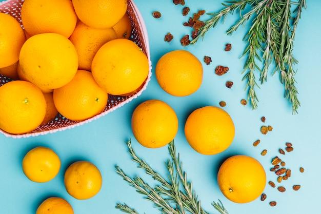 Gehele sinaasappelenvruchten en rozemarijn op blauwe achtergrond