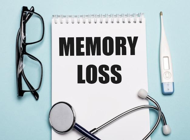 Geheugenverlies geschreven op een wit notitieblok naast een stethoscoop, een veiligheidsbril en een elektronische thermometer op een lichtblauw oppervlak. medisch concept.