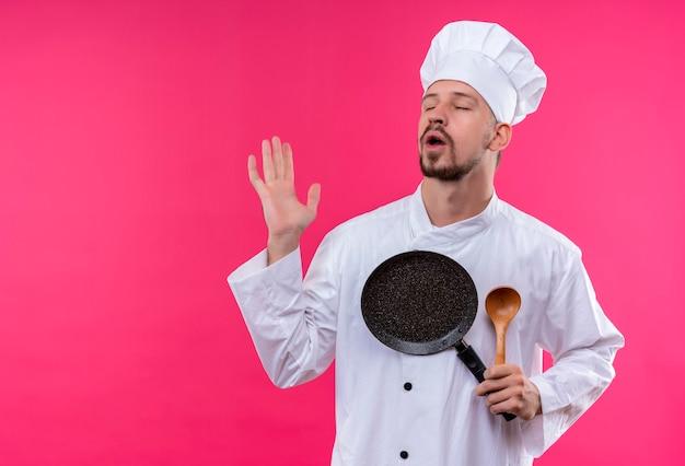 Gehinderd professionele mannelijke chef-kok in wit uniform en kok hoed met pan en houten lepel sluiten ogen permanent over roze achtergrond
