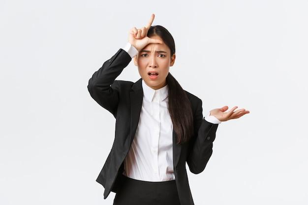 Gehinderde en geërgerde aziatische zakenvrouw die werknemer uitscheldt wegens mislukking, verliezersgebaar toont en hand in ontzetting opsteekt, kan niet begrijpen waarom zo dom, klagend over witte achtergrond