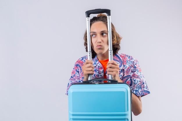 Gehinderde jonge reizigersmens die met koffer verwarde status kijkt