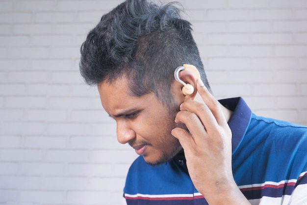 Gehoorapparaat concept, een jonge man met gehoorproblemen.