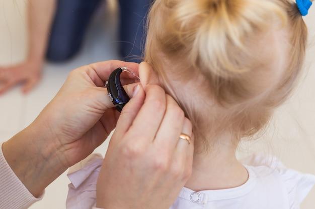 Gehoorapparaat in het oor van het babymeisje