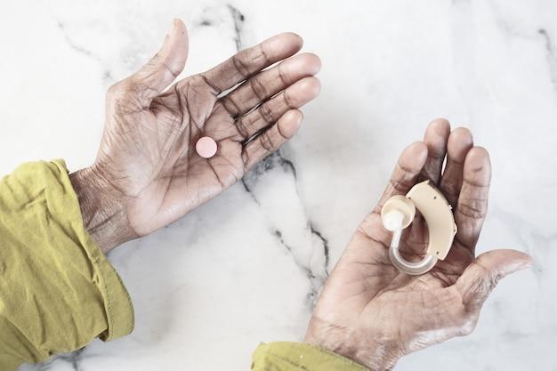 Gehoorapparaatapparatuur en pillen op de handpalm houden