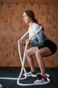 Gehurkt met een touw. sportieve jonge vrouw heeft fitnessdag in de sportschool in de ochtendtijd