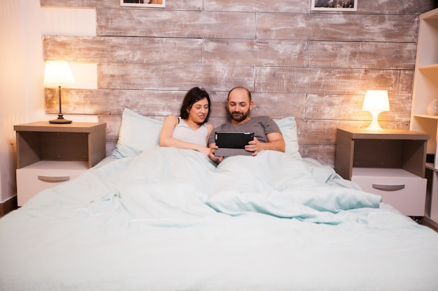 Gehuwd kaukasisch paar die pyjama's dragen die tabletcomputer gebruiken vóór slaap.