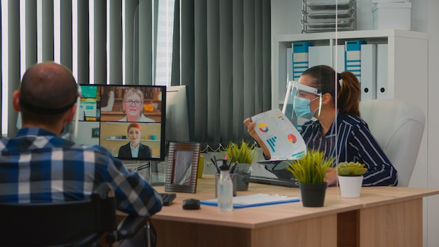 Geïmmobiliseerde freelancer met beschermingsmasker in rolstoel met videovergadering tijdens een coronaviruspandemie in een nieuw normaal bedrijfskantoor. freelancer die in bedrijf werkt met respect voor sociale afstand.