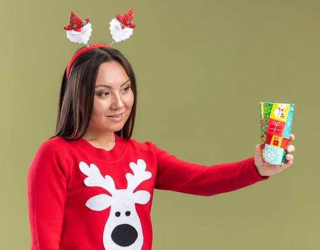 Geïmponeerd jong aziatisch meisje dat de hoepel van het kerstmishaar draagt die kerstmiskop aan kant houdt die op olijfgroene muur wordt geïsoleerd