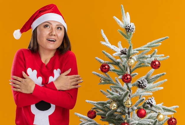 Geïmponeerd jong aziatisch meisje dat kerstmishoed met sweater draagt die zich dichtbij kerstboom bevindt die handen kruist die op oranje achtergrond worden geïsoleerd