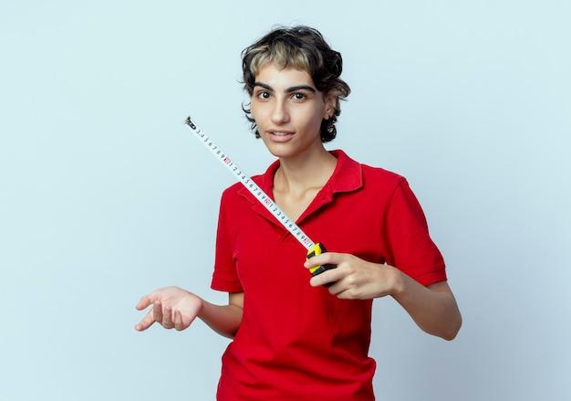 Geïmponeerd jong kaukasisch meisje met pixiekapsel die de bandmeter houden die hand in lucht houden die op witte achtergrond wordt geïsoleerd