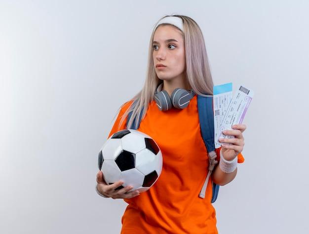 Geïmponeerd jong kaukasisch sportief meisje met hoofdtelefoons om hals die rugzakhoofdband draagt
