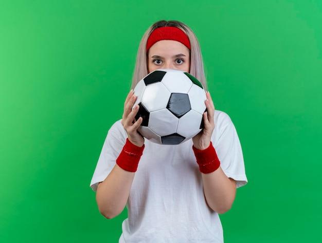 Geïmponeerd jong kaukasisch sportief meisje met steunen die hoofdband dragen