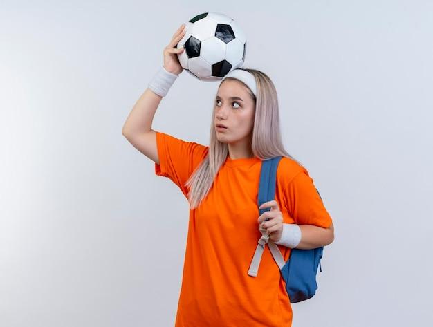 Geïmponeerd jong kaukasisch sportief meisje met steunen die rugzakhoofdband en polsbandjes dragen