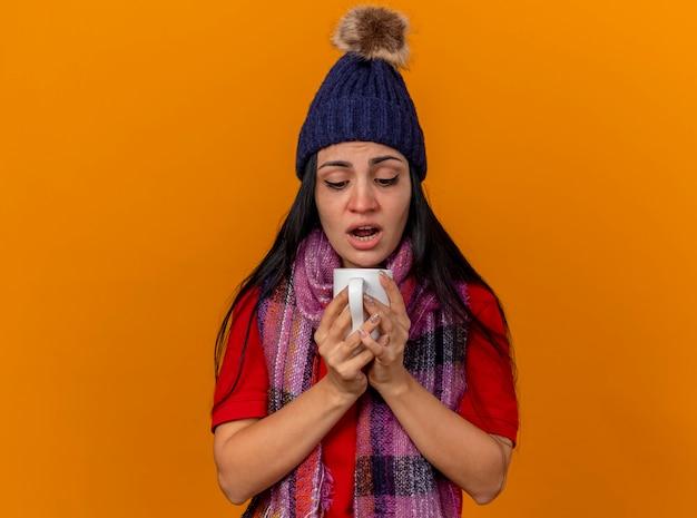 Geïmponeerd jong kaukasisch ziek meisje die de winterhoed en sjaal dragen die kop thee houden die binnenkop kijken die op oranje achtergrond met exemplaarruimte wordt geïsoleerd