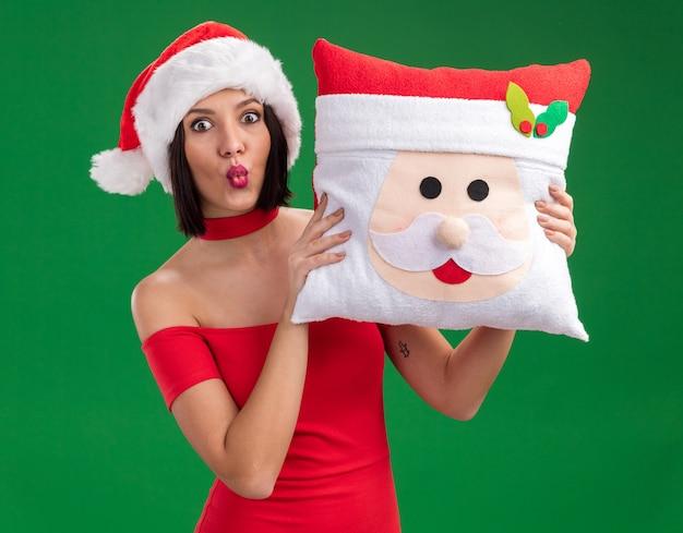 Geïmponeerd jong meisje dat santahoed draagt die het hoofdkussen van de kerstman met samengeknepen lippen houdt die op groene muur worden geïsoleerd
