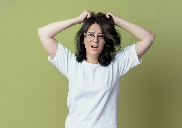 Geïmponeerd jong vrij kaukasisch meisje die glazen dragen die haar die haar trekken op olijfgroene achtergrond wordt geïsoleerd
