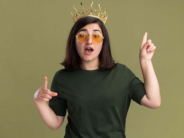 Geïmponeerd jong vrij kaukasisch meisje in zonnebril met kroon die met twee handen op olijfgroen benadrukt