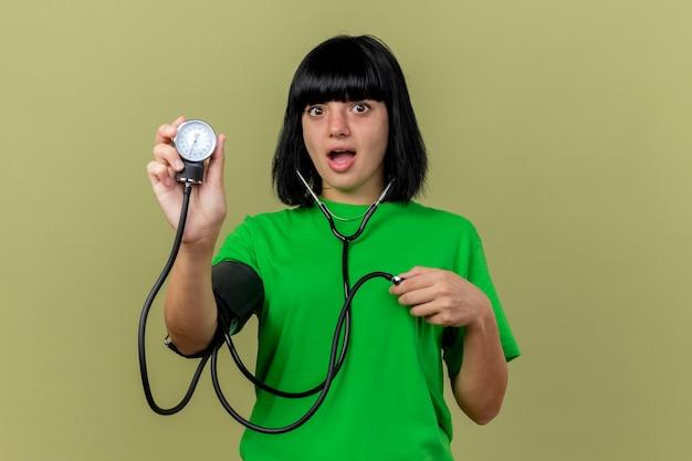 Geïmponeerd jong ziek kaukasisch meisje dat stethoscoop draagt die bloeddrukmeter toont die op olijfgroene muur met exemplaarruimte wordt geïsoleerd