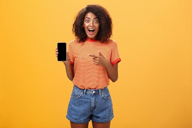Geïmponeerde afro-amerikaanse vrouw met krullend haar wijzend op mobiel over oranje muur