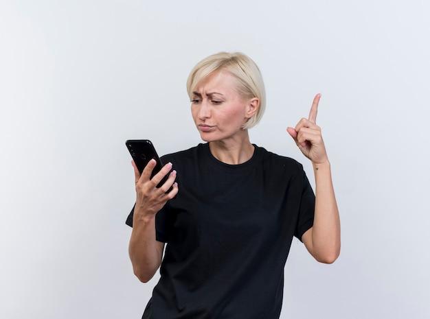 Geïmponeerde blonde slavische vrouw die op middelbare leeftijd en mobiele telefoon houdt die vinger opheft die op witte achtergrond met exemplaarruimte wordt geïsoleerd