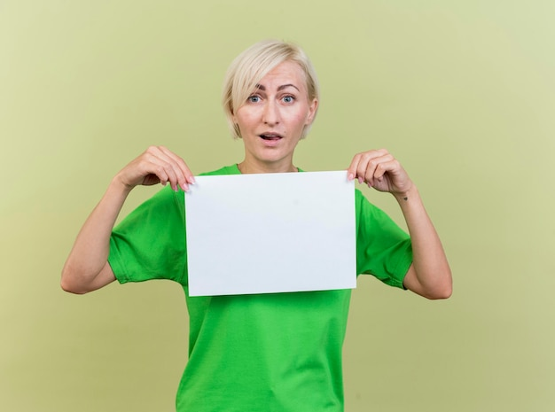 Geïmponeerde blonde slavische vrouw die van middelbare leeftijd leeg document houdt die voorzijde bekijkt die op olijfgroene muur wordt geïsoleerd