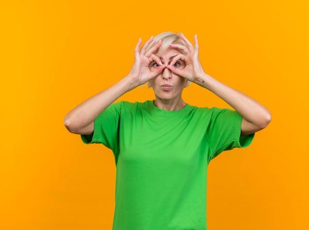 Geïmponeerde blonde slavische vrouw die van middelbare leeftijd naar voorzijde kijkt die blikgebaar doet met handen als verrekijker die op gele muur wordt geïsoleerd