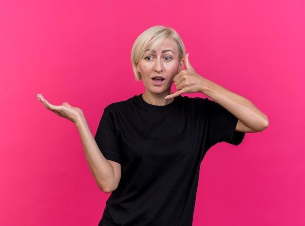 Geïmponeerde blonde slavische vrouw van middelbare leeftijd die lege hand toont die kant bekijkt die vraaggebaar doet dat op roze muur wordt geïsoleerd