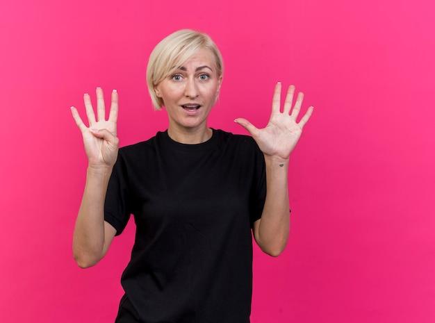 Geïmponeerde blonde slavische vrouw van middelbare leeftijd die voorzijde bekijkt die negen met handen toont die op roze muur met exemplaarruimte worden geïsoleerd