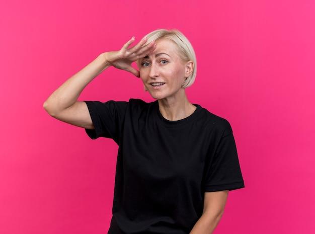 Geïmponeerde blonde vrouw die van middelbare leeftijd hand op voorhoofd houdt die afstand aan voorzijde onderzoeken die op roze muur wordt geïsoleerd