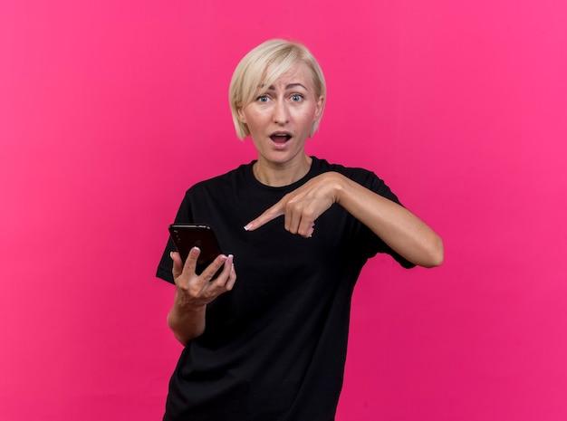 Geïmponeerde blonde vrouw van middelbare leeftijd die en op mobiele telefoon houdt richt die voorzijde bekijkt die op roze muur wordt geïsoleerd