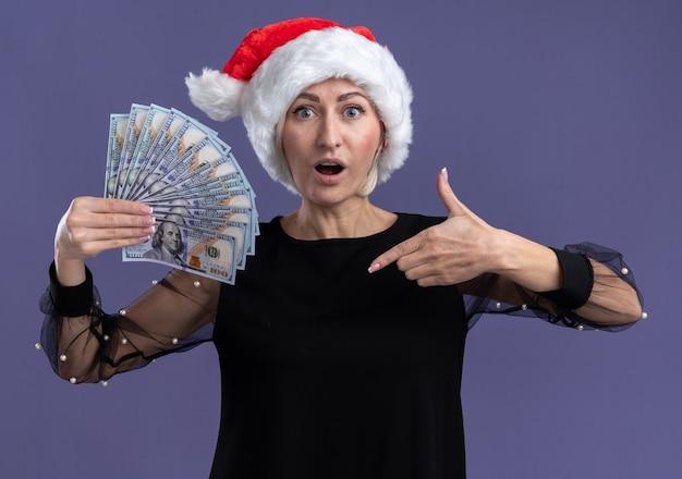 Geïmponeerde blonde vrouw van middelbare leeftijd die kerstmishoed draagt en op geld richt die camera bekijkt die op purpere achtergrond wordt geïsoleerd