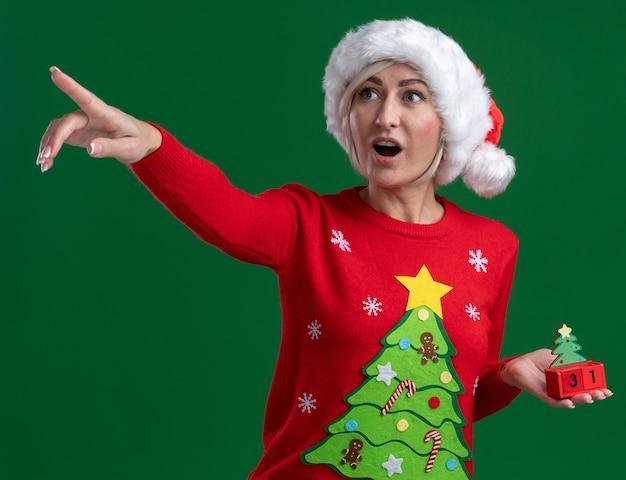 Geïmponeerde blonde vrouw van middelbare leeftijd die kerstmishoed en sweater draagt die de kerstboomstuk speelgoed met datum kijkt en naar kant kijkt die op groene achtergrond wordt geïsoleerd