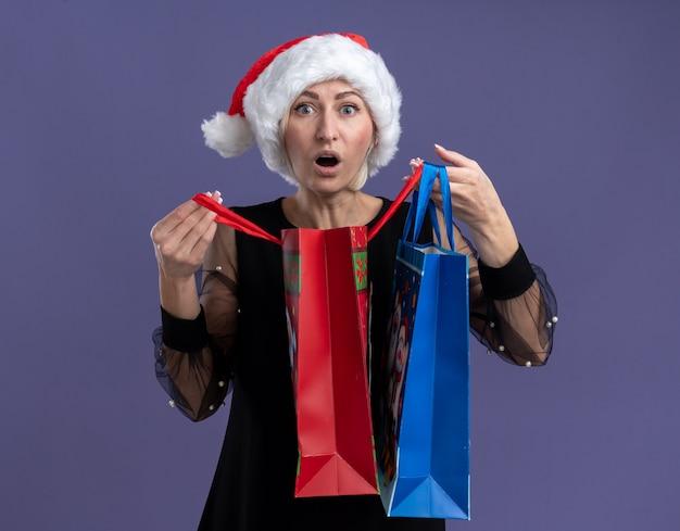 Geïmponeerde blonde vrouw van middelbare leeftijd die kerstmuts draagt die de zakken van de kerstmisgift houdt die één openen die camera bekijken die op purpere achtergrond wordt geïsoleerd