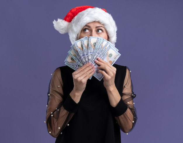 Geïmponeerde blonde vrouw van middelbare leeftijd die kerstmuts draagt die geld houdt die kant van achteren bekijkt die op purpere muur met exemplaarruimte wordt geïsoleerd