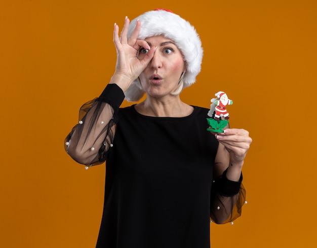 Geïmponeerde blonde vrouw van middelbare leeftijd die kerstmuts draagt en kijkt naar het stuk speelgoed van de kerstman van de kantholding die blikgebaar doet dat op oranje achtergrond wordt geïsoleerd