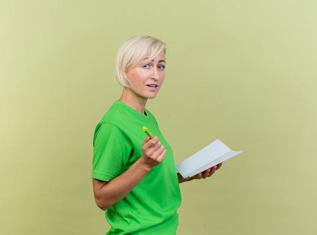 Geïmponeerde blonde vrouw van middelbare leeftijd die zich in profielmening bevindt die notitieblok wijst naar voorzijde met pen die op olijfgroene muur wordt geïsoleerd
