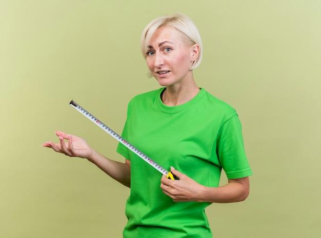 Geïmponeerde blonde vrouw van middelbare leeftijd die zich in profielmening bevindt die voorholding bandmeter bekijkt die lege hand toont die op olijfgroene muur wordt geïsoleerd