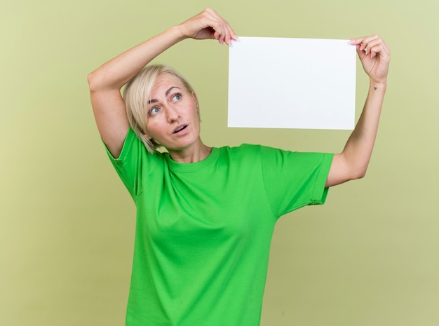 Geïmponeerde blonde vrouw van middelbare leeftijd met blanco papier in de buurt van het hoofd te kijken naar het geïsoleerd op olijfgroene muur