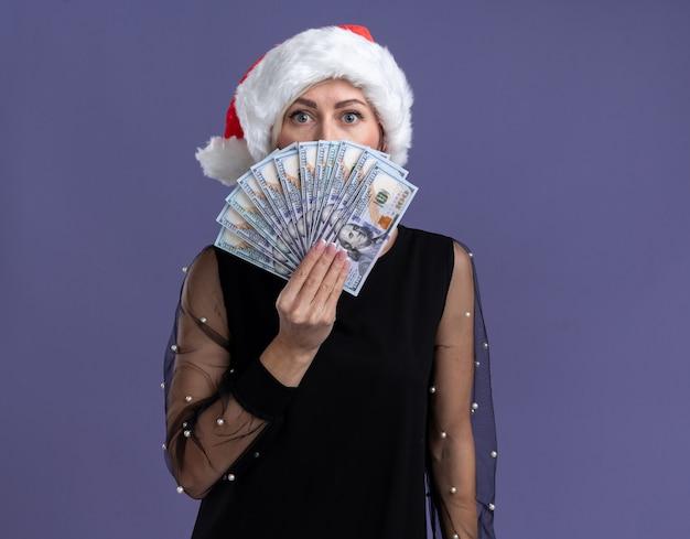 Geïmponeerde blonde vrouw van middelbare leeftijd met kerstmuts met geld van achteren geïsoleerd op paarse muur met kopie ruimte