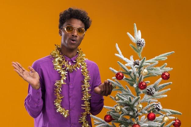 Geïmponeerde jonge afro-amerikaanse man met bril met klatergoud slinger rond de nek staande in de buurt van versierde kerstboom op oranje achtergrond