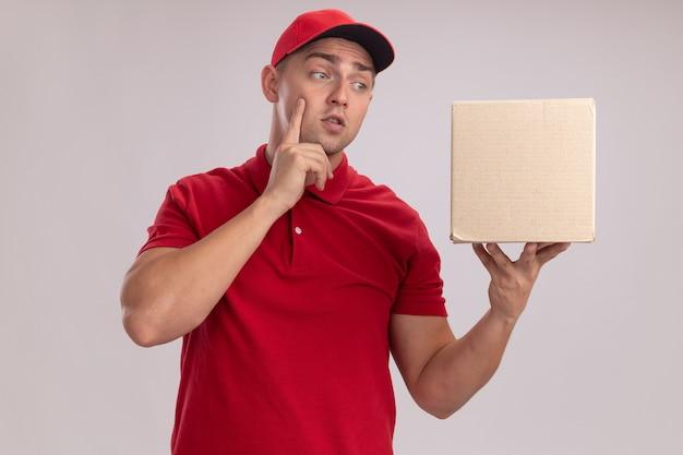 Geïmponeerde jonge bezorger die uniform met pet draagt en doos bekijkt die op witte muur wordt geïsoleerd