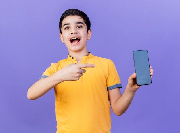 Geïmponeerde jonge blanke jongen die en op mobiele telefoon toont die op purpere muur wordt geïsoleerd