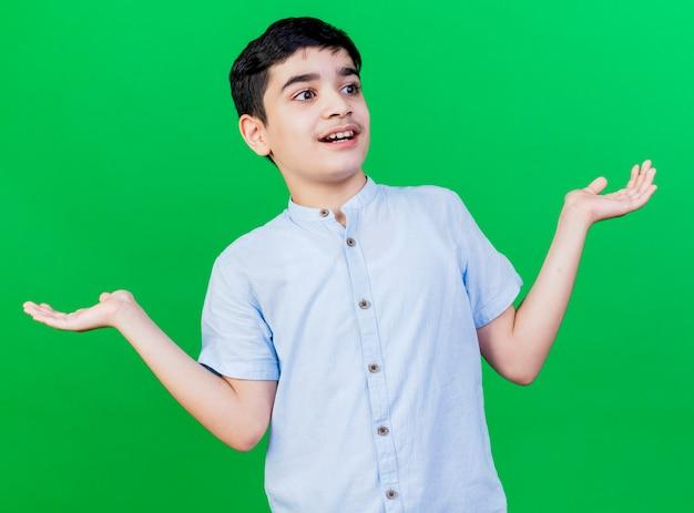 Geïmponeerde jonge blanke jongen die kant kijkt die lege handen toont die op groene muur worden geïsoleerd