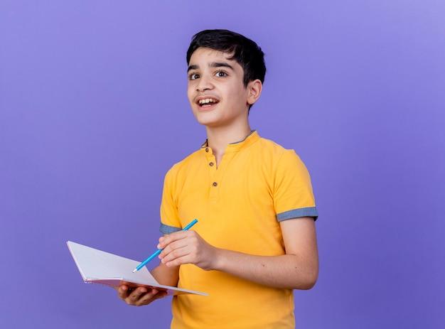 Geïmponeerde jonge blanke jongen met notitieblok en potlood geïsoleerd op paarse muur met kopie ruimte