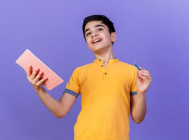 Geïmponeerde jonge blanke jongen met notitieblok en potlood geïsoleerd op paarse muur