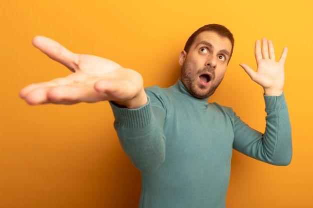 Geïmponeerde jonge blanke man die uit hand strekt die lege hand toont die omhoog geïsoleerd op oranje muur kijkt